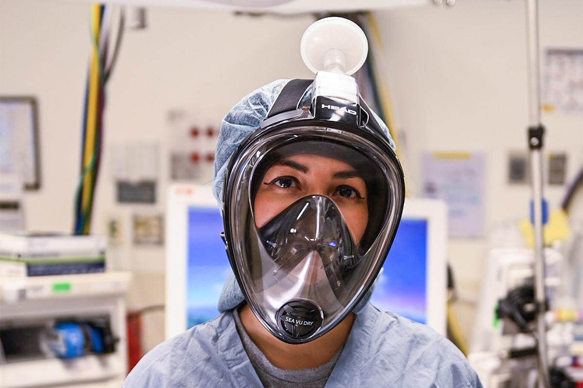 Healthcare worker wearing a snorkel mask converted to meet clinical specifications