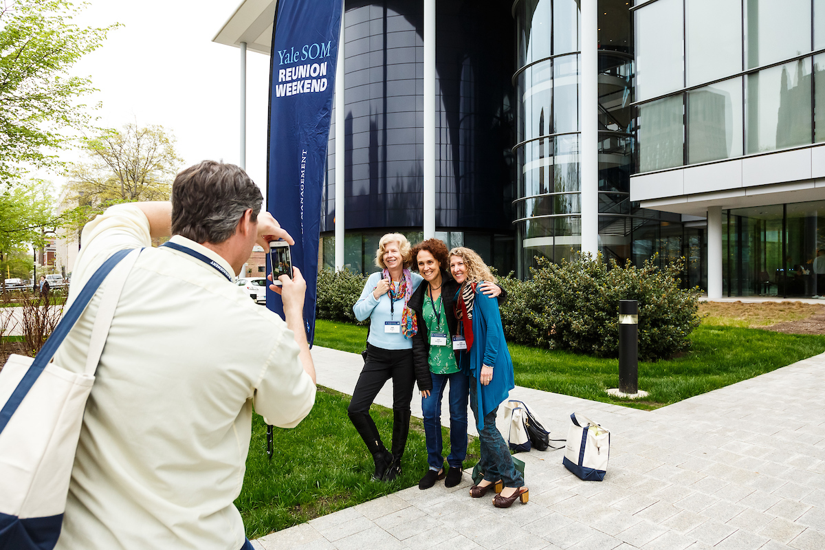Alumni taking a photo in front of Edward P. Evans Hall