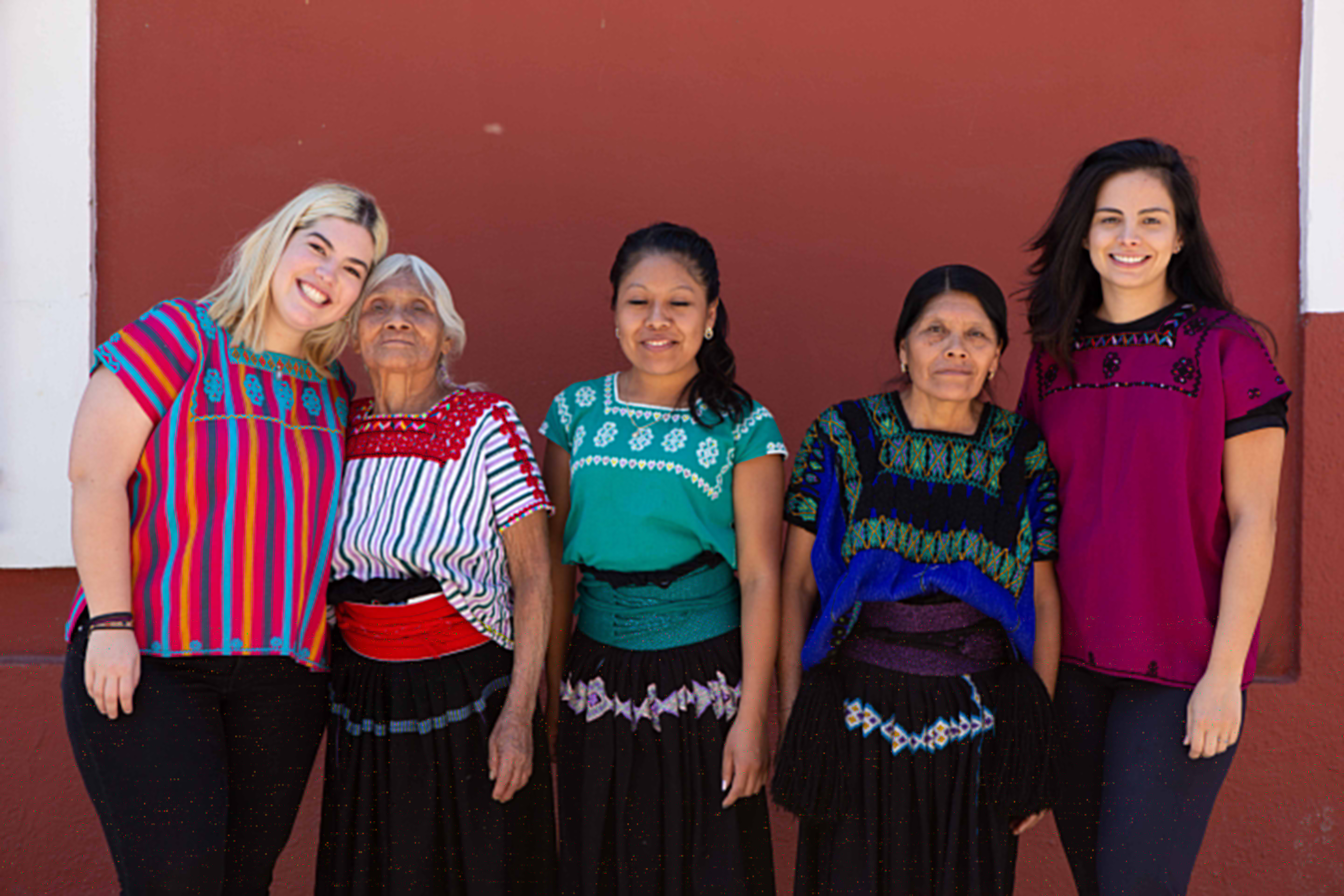 Members of the Amor and Rosas team pose with the artisans