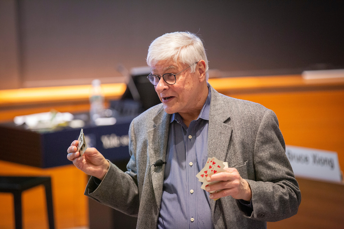 Professor Roger Ibbotson talking while holding playing cards