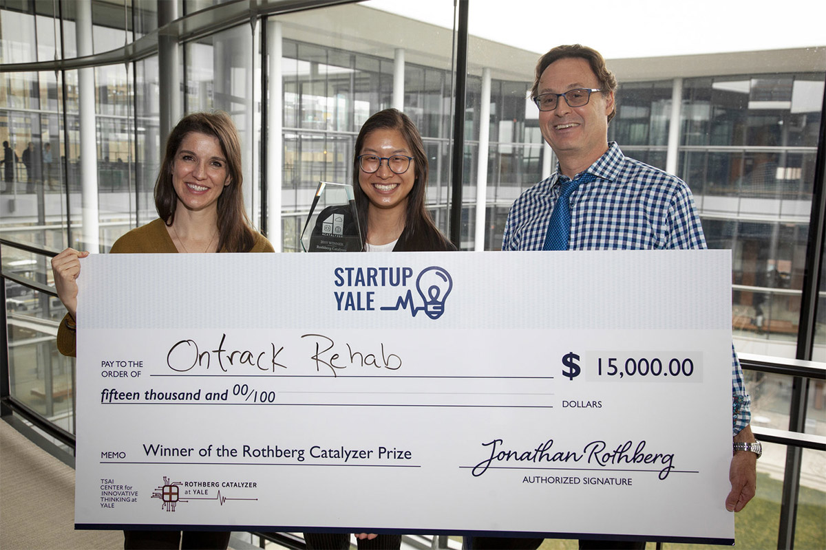 three people hold a large check made out to OnTrack Rehab