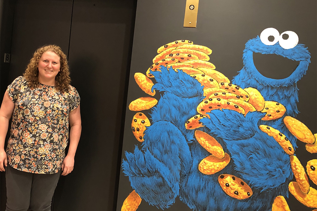 Standing in front of a mural featuring Cookie Monster