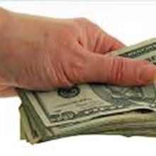 A hand holding a wad of money.