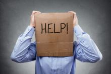 Man with box on head that says help!